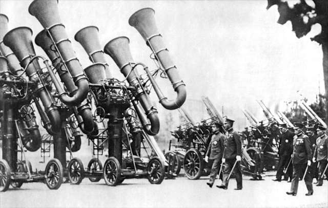 "1930s Three Japanese acoustic locators, colloquially known as ""war tubas,"" mounted on four-wheel carriages, being inspected by Japanese Emperor Shōwa. IMAGE: PUBLIC DOMAIN"