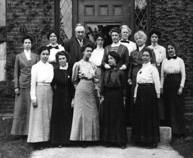 Photograph of the Harvard Computers, a group of women who worked under Edward Charles Pickering at the Harvard College Observatory. The photograph was taken on 13 May 1913 in front of Building C, which was then the newest building at the Observatory. The image was discovered in an album which had once belonged to Annie Jump Cannon. Image courtesy of the Harvard-Smithsonian Center for Astrophysics. Back row (L to R): Margaret Harwood (far left), Mollie O'Reilly, Edward C. Pickering, Edith Gill, Annie Jump Cannon, Evelyn Leland (behind Cannon), Florence Cushman, Marion Whyte (behind Cushman), Grace Brooks. Front row: Arville Walker, unknown (possibly Johanna Mackie), Alta Carpenter, Mabel Gill, Ida Woods (Source: Harvard-Smithsonian Center for Astrophysics. This media file is in the public domain because its copyright has expired).
