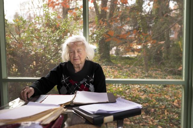 Sitting in her sunroom, Dr. Karle reviews her husband's research documents and publications.