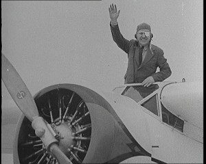 "Wiley Post waving to the crowd before taking off to make the first solo flight around the world. As he waved, he said ""So long, see you in about six days!"" Credit: Still taken from British Pathé newsreel 1933."