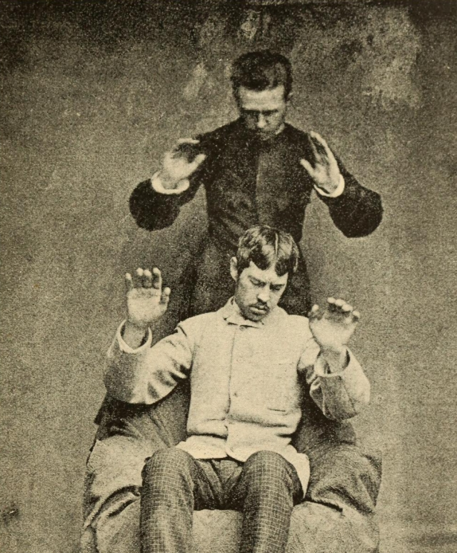 Detail from a depiction of thought-transference, the man behind dictating the movement of the other, from Magnetismus und Hypnotismus (1895) by Gustav Wilhelm Gessmann