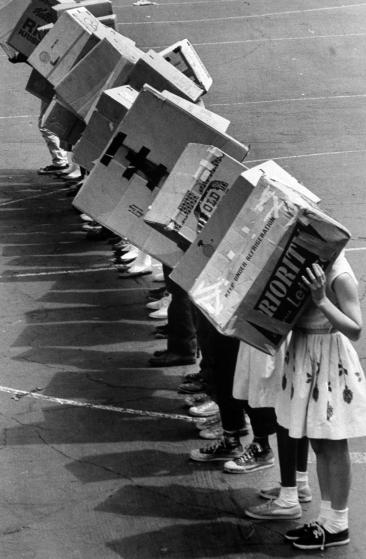 Caption from LIFE. Fifth-graders at the Emerson School in Maywood, Ill. line up with backs to the sun and their eclipse-watching boxes over their heads. Francis Miller—The LIFE Picture Collection/Getty Images