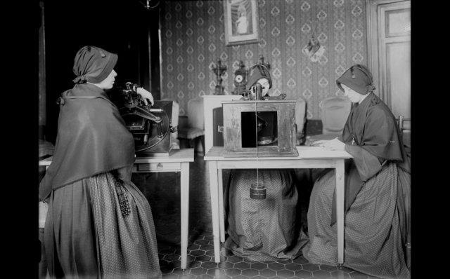 Members of the Sisters of the Child Mary use microscopes to review glass plates as they measure star positions. (CNS/Vatican Observatory)