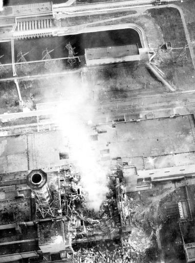 Aerial view of the damaged core on 3 May 1986. Roof of the turbine hall is damaged (image center). Roof of the adjacent reactor 3 (image lower left) shows minor fire damage. Source: Wikimedia Commons