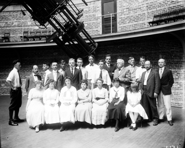 Yerkes Observatory staff, August 1916, from left (back row, standing): Stanley H. Hughes, Everett I. Yowell, Julius Lemkowitz, John A. Parkhurst, John Mellish, Clifford Crump, Max Petersen, Oliver J. Lee, Lloyd R. Wylie, Edwin Hubble, Edward Emerson Barnard, Edwin Brant Frost (Director), Francis Easton Carr, Francis P. Leavenworth, Storrs B. Barrett; (front row, seated) Esther Wendell, Mary Ross Calvert, Evelyn W. Wickham, Vera Gushee, Frances Lowater, Elise Johns, Mrs. Mellish's sister (unnamed). University of Chicago Photographic Archive