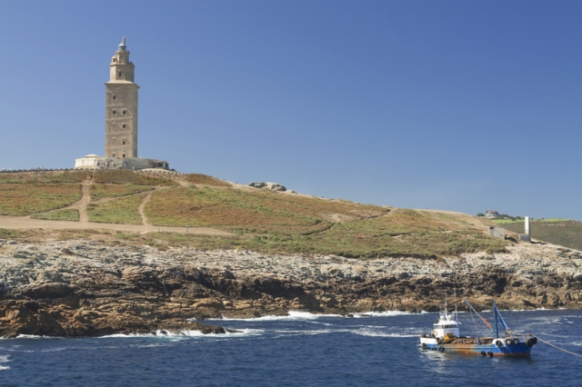 Spain, Galicia, A Coruna, Hercules Tower Lighthouse, in daylight, clear sky, Atlantic Ocean waters, a boat