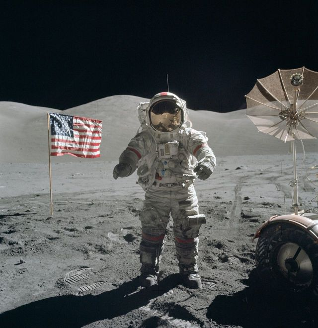 In December of 1972, Apollo 17 astronauts Eugene Cernan and Harrison Schmitt spent about 75 hours on the Moon in the Taurus–Littrow valley. Near the beginning of their third and final excursion across the lunar surface, Schmitt took this picture of Cernan flanked by an American flag and their lunar rover's umbrella-shaped high-gain antenna. The prominent Sculptured Hills lie in the background while Schmitt's reflection can just be made out in Cernan's helmet. NASA / Harrison H. Schmitt Source: Wikimedia Commons