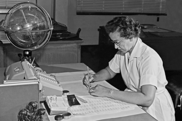 Katherine Johnson sits at her desk with a calculating machine and a special globe known as a celestial training device. Credit: NASA